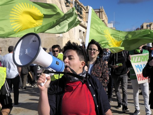 Mina Tolu at the foreground of the photo holds a white and blue megaphone that they talk into. Behind them are other protestors holding green and yellow flags and posters.
