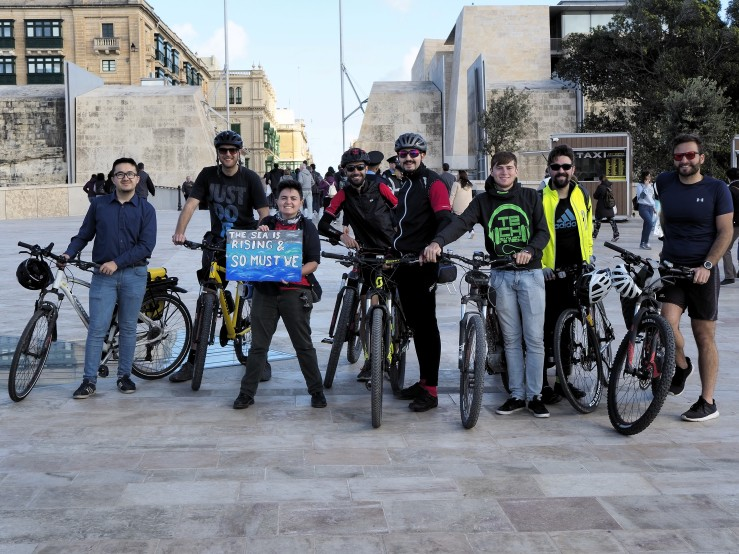 A group photo of Mina who stands holding a poster, next to 7 men and 7 bikes. Some of them wearing helmets and sunglasses.