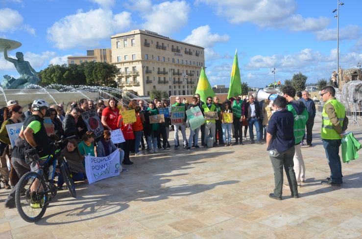 A group of around 70 protestors holding up different slogans and banners standing in front of the Triton fountain in Valletta.