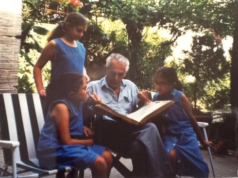 A man with white hair sits down on a garden chair. A girl with long blonde hair tied up in a ponytail peers over his shoulder standing behind him. Two identical twins sit either side of him. One looks at the other, who looks at the book which is held in their Grandfather's hands.